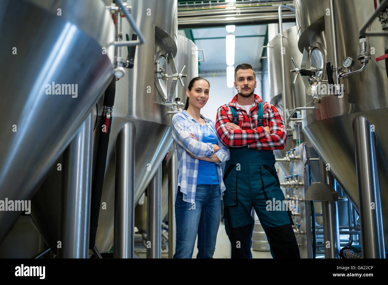 Brewers standing at brewery - Stock Image