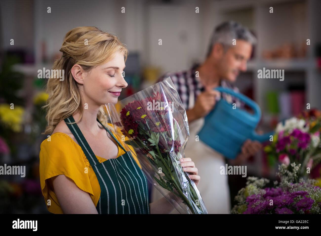 Happy female florist smelling a flower bouquet Stock Photo