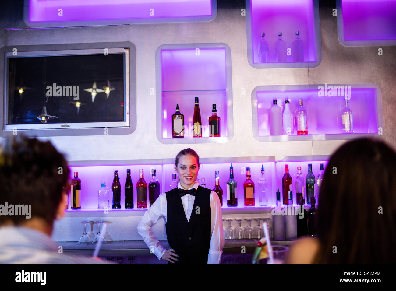Barmaid standing with hand on hip on bar counter - Stock Image