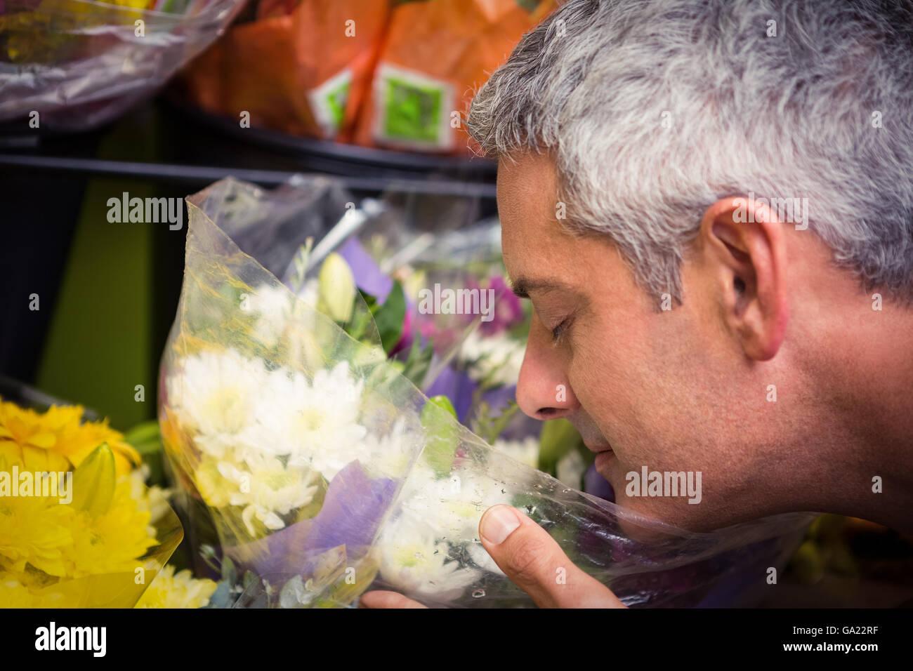 Male florist smelling flower - Stock Image