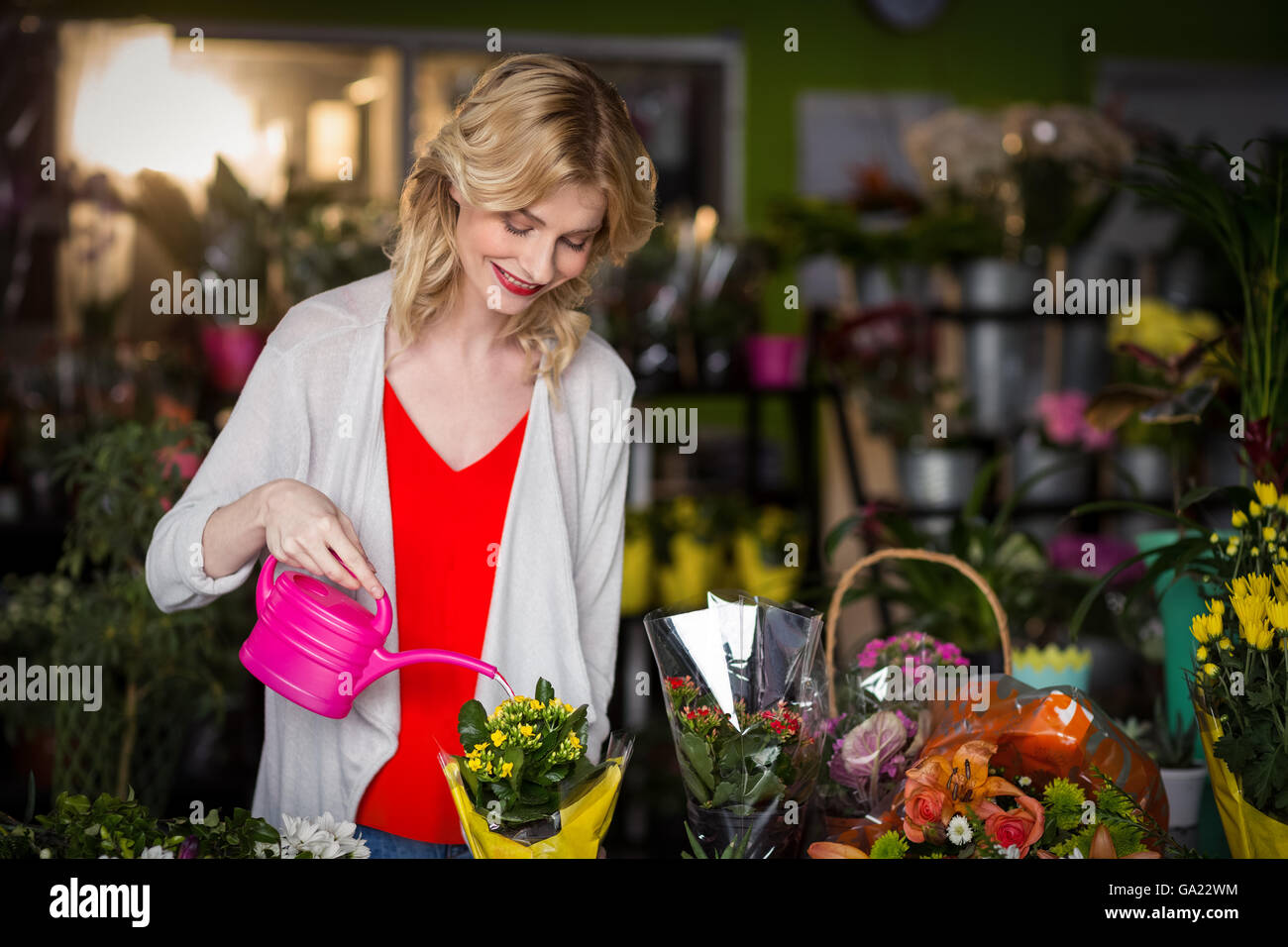 Female florist watering flowers - Stock Image