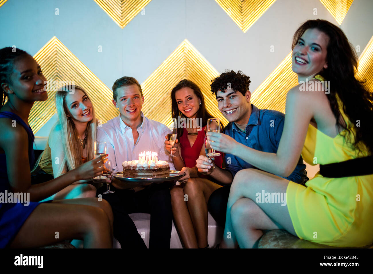 Group of smiling friends having a glass of champagne while celebrating birthday - Stock Image