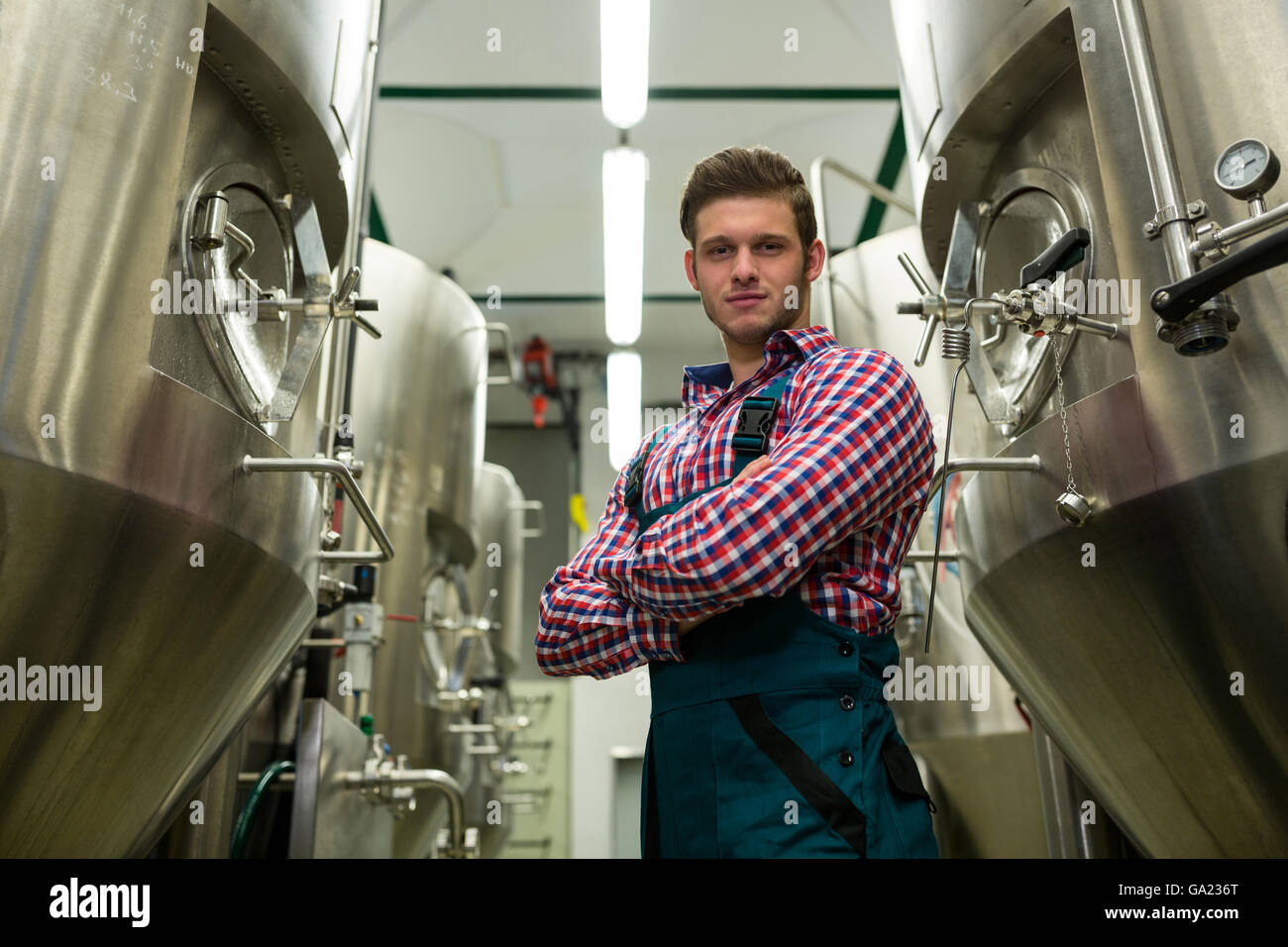 Brewer with arms crossed at brewery - Stock Image
