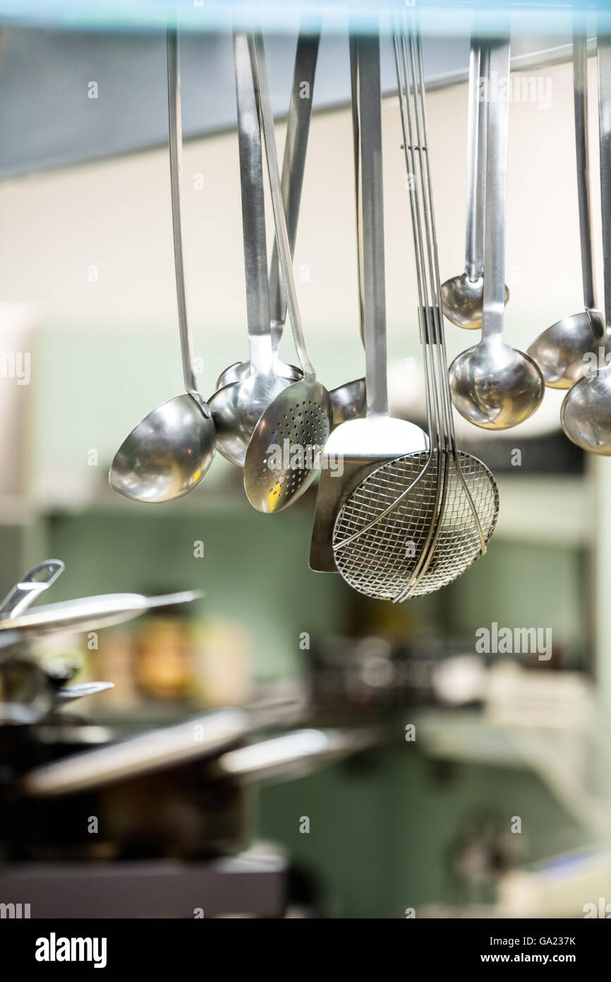 Close-up of hanging kitchen utensils - Stock Image