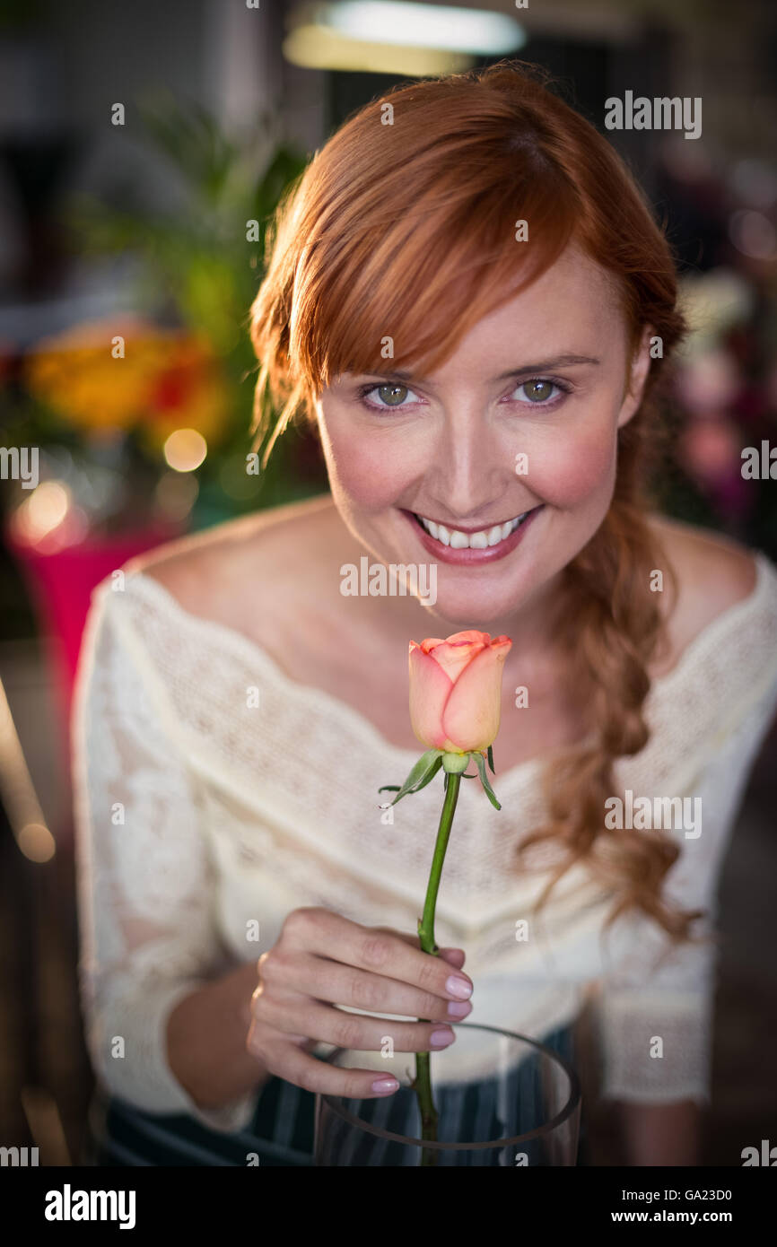 Portrait of female florist smelling a rose flower Stock Photo