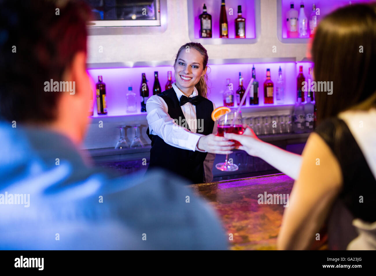 Barmaid serving drink to woman - Stock Image