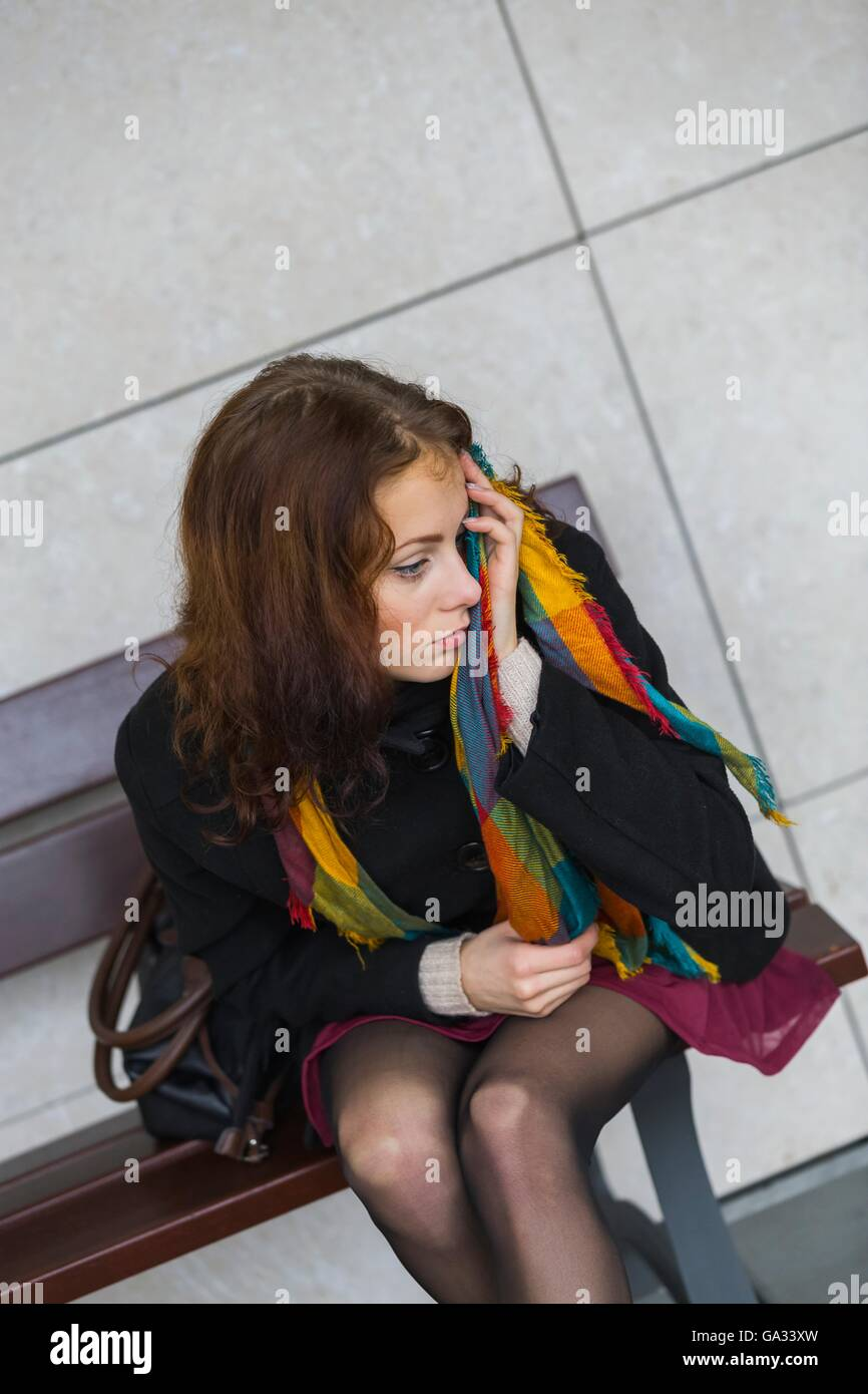 In bad mood teenager adult sitting on bench on street looking away urban lifestyle single sits upset desperate desperation - Stock Image