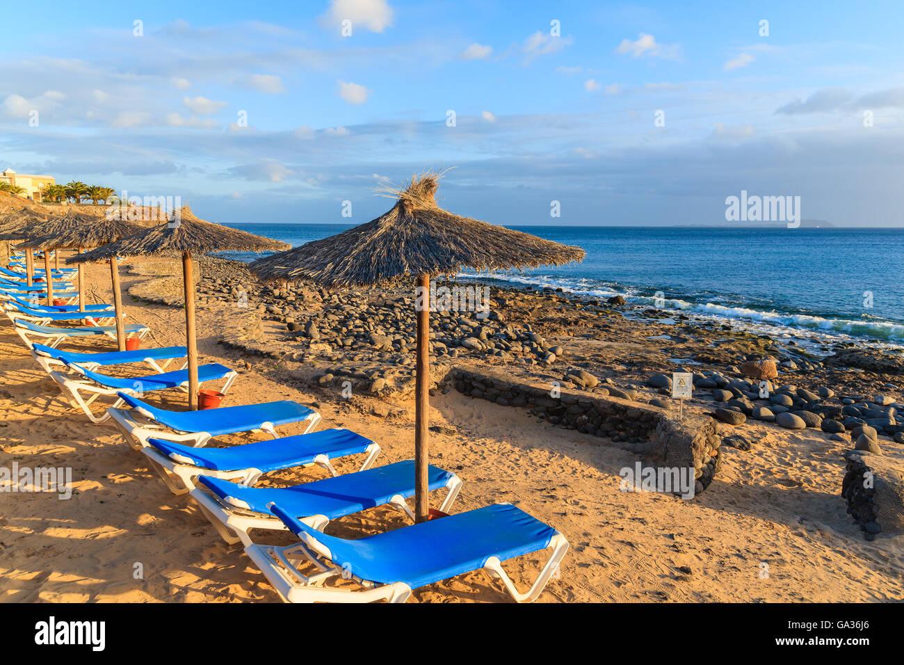Row Of Sunbeds And Umbrellas On Playa Blanca Beach At Sunset
