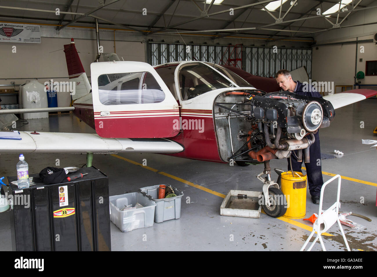 An aircraft engineer working on the engine of a light aircraft in a maintenance hangar. - Stock Image