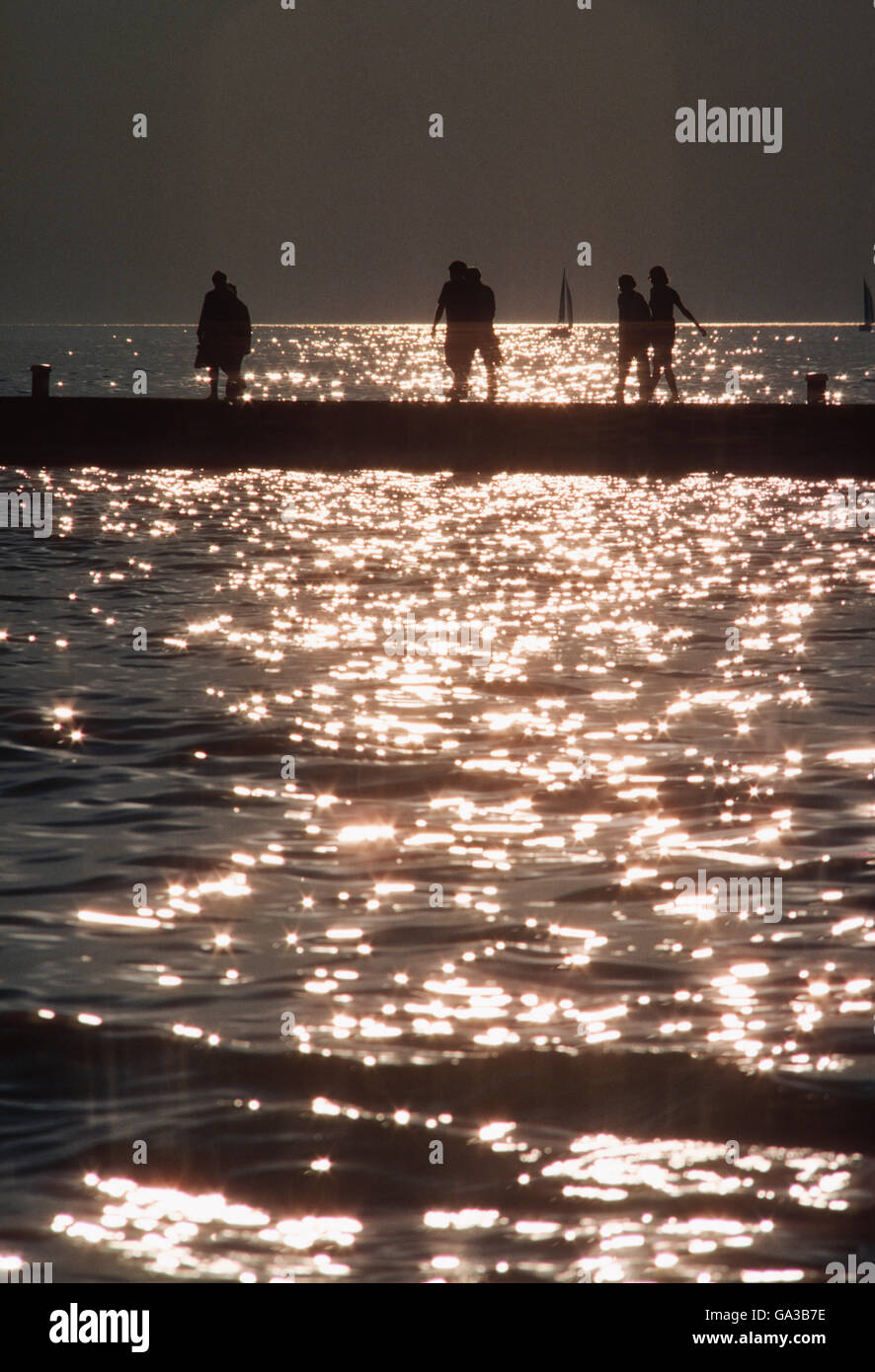 Vacationers silhouetted against reflections of setting sun on Lake Michigan; Michigan; USA - Stock Image