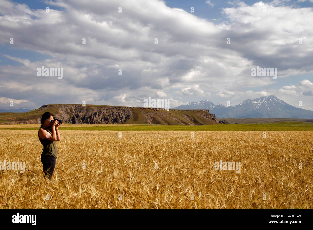 The photographer girl who is capturing Cappadocia's field on the background Hasandag Mountain and amazing sky. - Stock Image