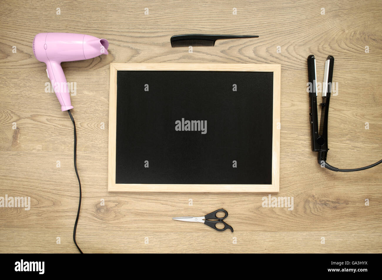 Hair dryer, iron, comb, scissors and blackboard on wooden background - Stock Image