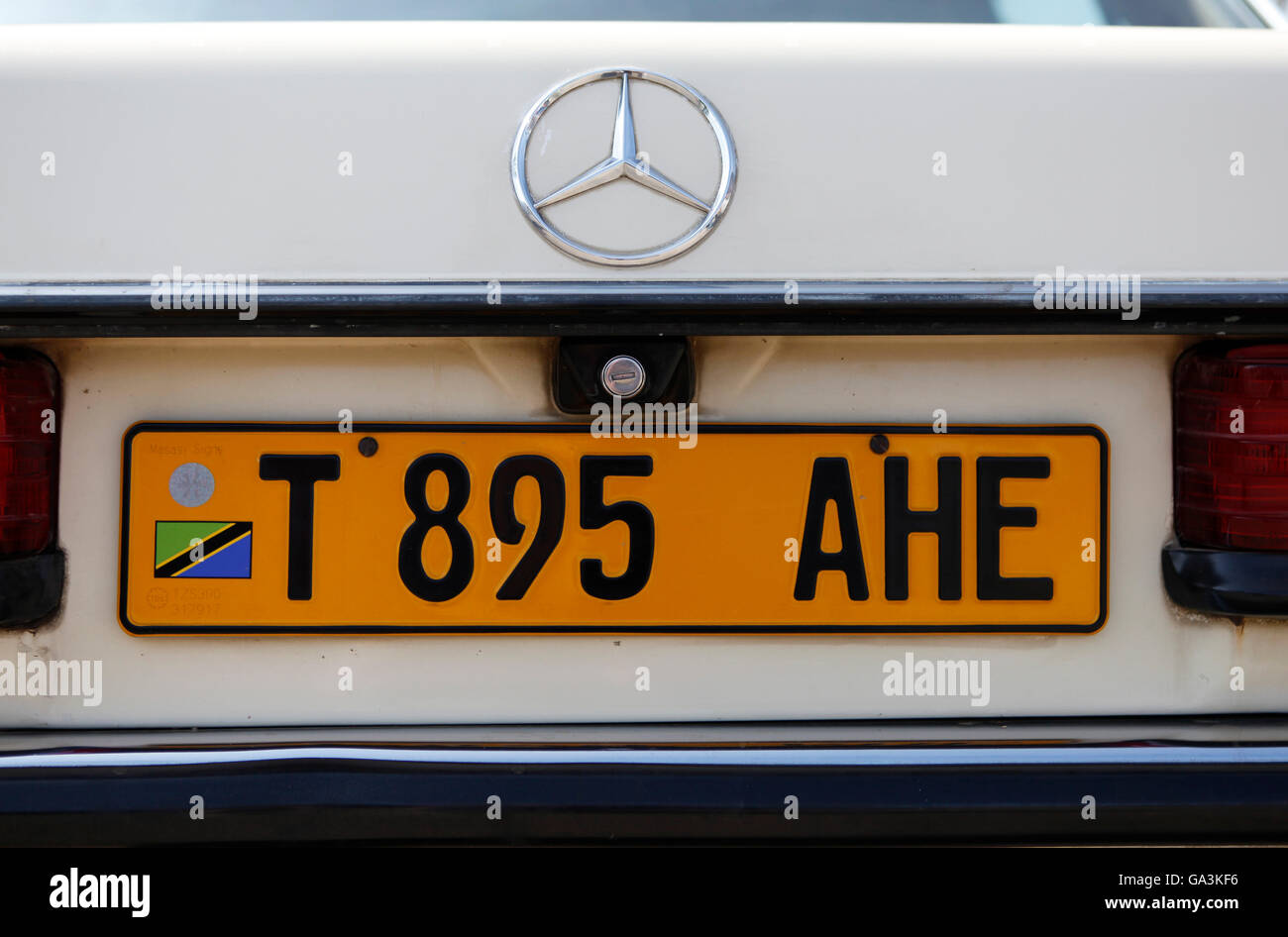 Yellow Tanzanian license plate on an old Mercedes in Tanzania, East Africa, Africa - Stock Image
