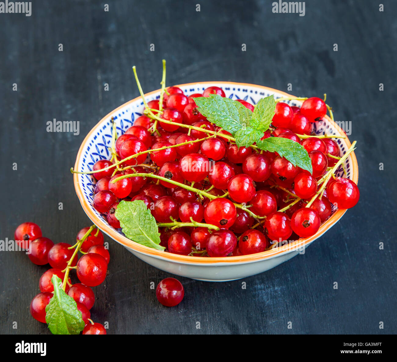 Red fresh currants in a rustic bowl with mint leaves - Stock Image