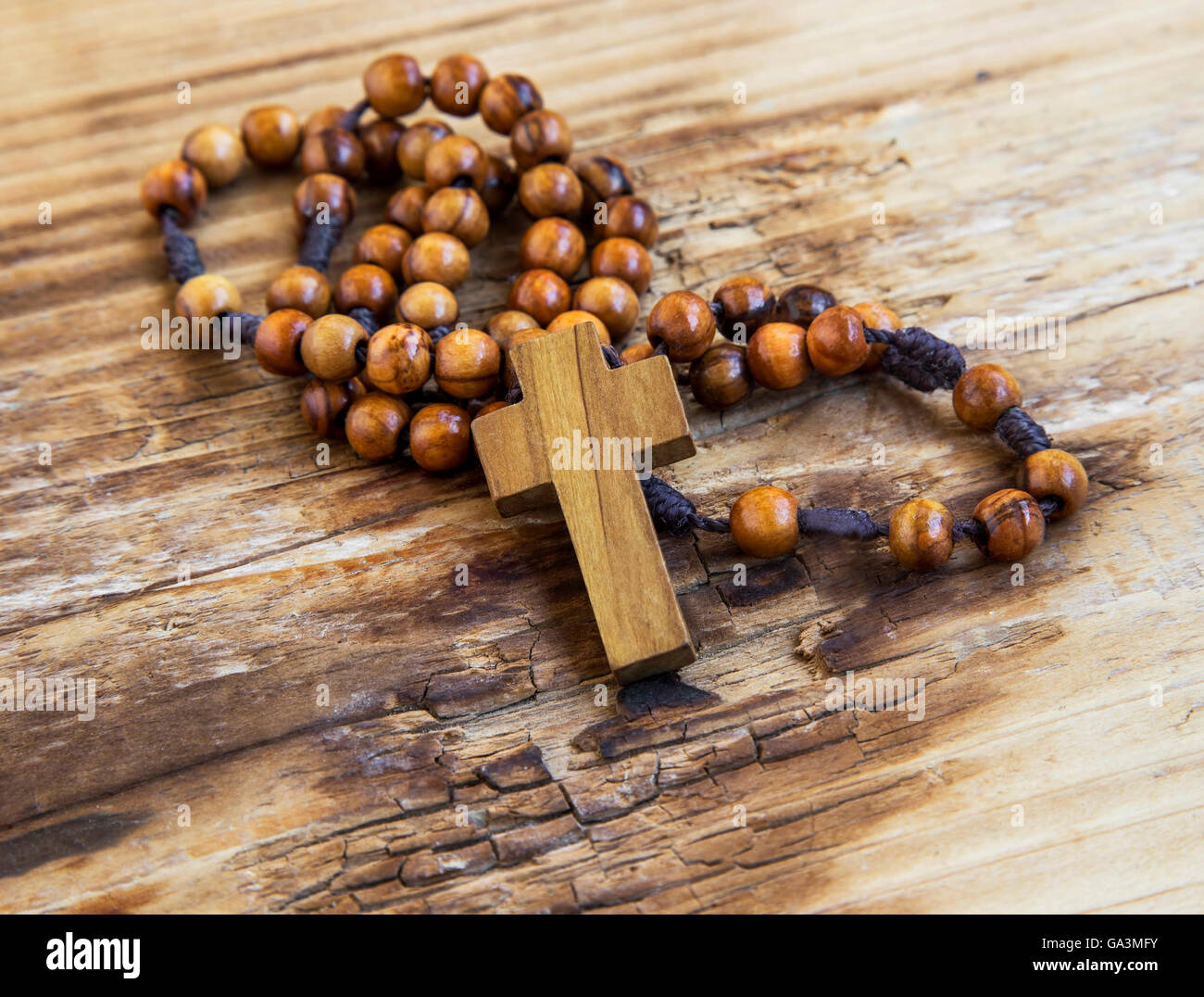 Wooden crucifix with rosary.Christianity symbol on wooden background - Stock Image