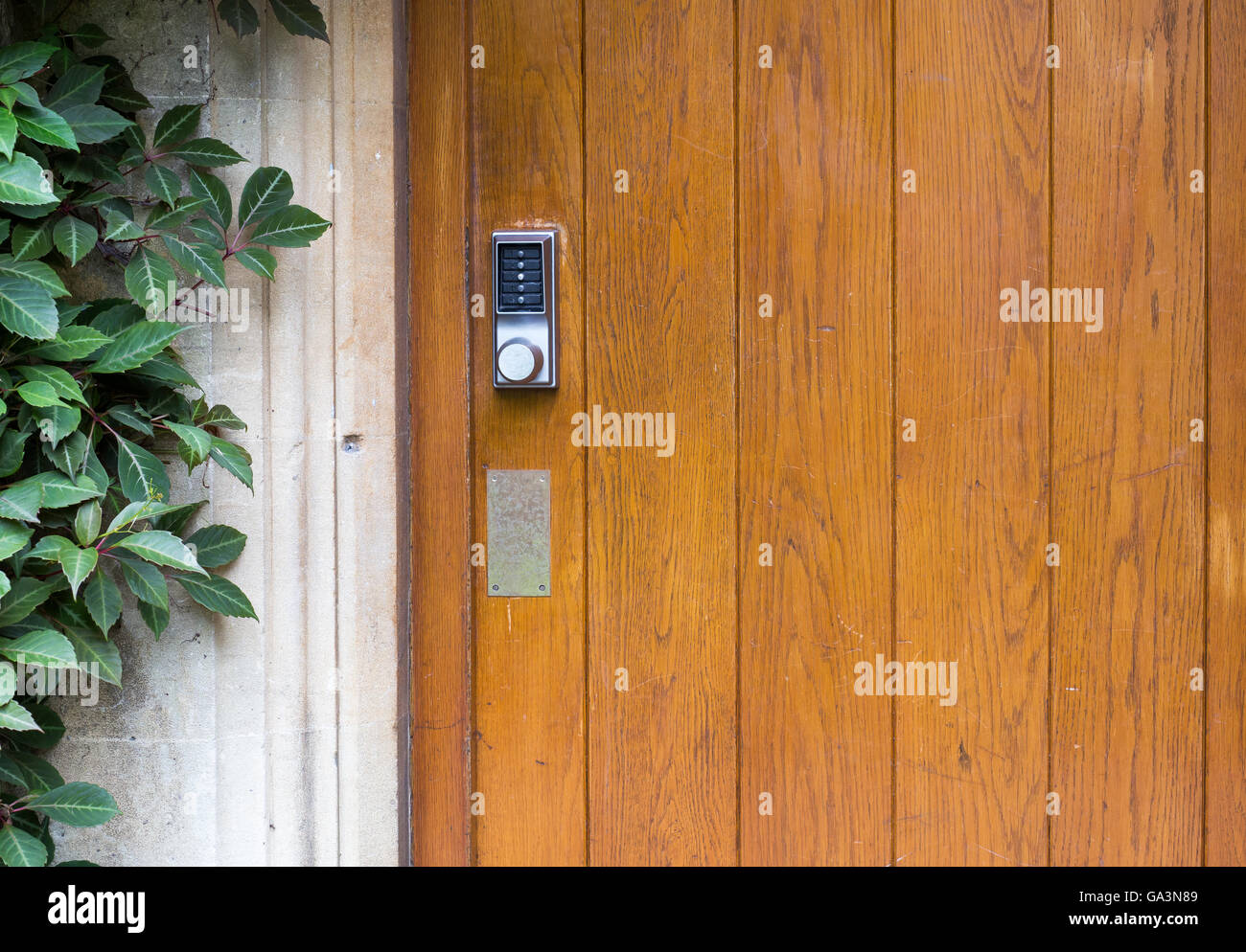 Simple door handle electronic lock with numeric buttons on old wooden door - Stock Image