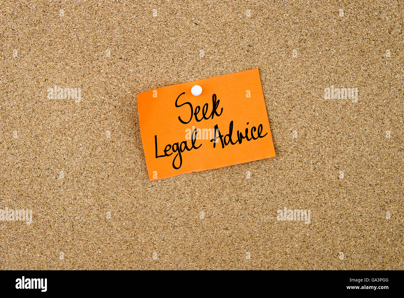 Seek Legal Advice written on orange paper note note pinned on cork board with white thumbtack, copy space available - Stock Image