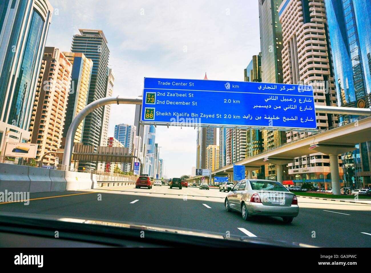City of Dubai. Road signs driving along city centre Sheikh Zayed Road. Al Yaquob Tower in distance. United Arab - Stock Image