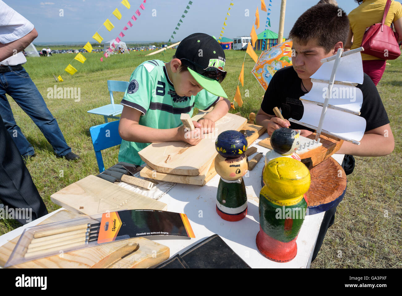 Two children crafting woodwork by hard carving - Stock Image