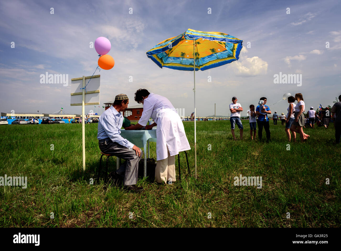 Man having a blood pressure check outside by a nurse - Stock Image