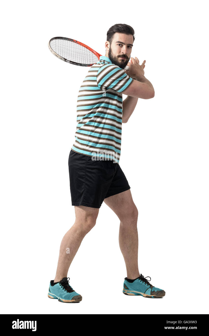 Tennis player waiting to hit ball holding racket with both hands in backhand pose. Full body length portrait isolated - Stock Image