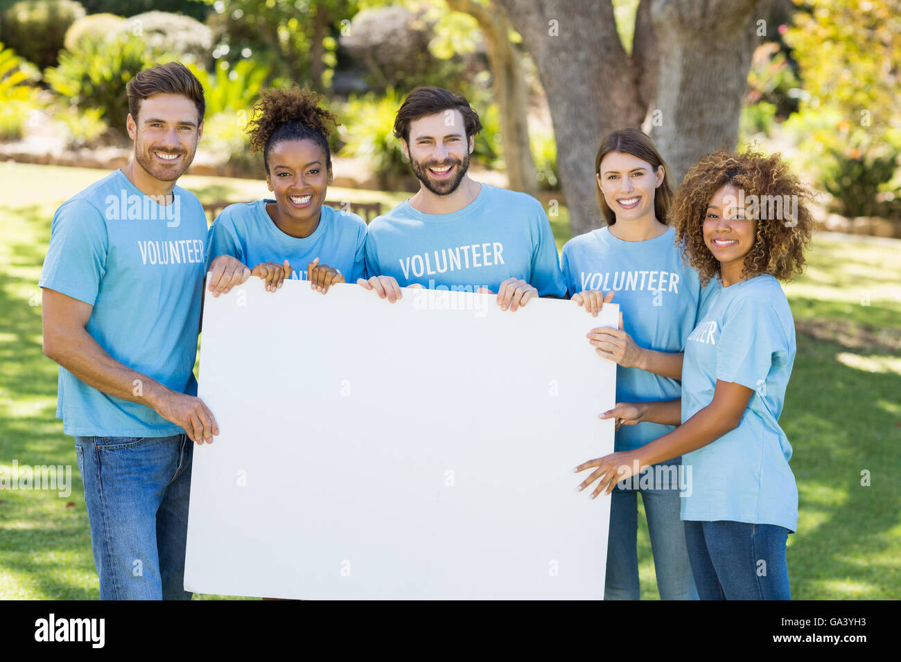 Portrait of volunteer group holding blank sheet - Stock Image