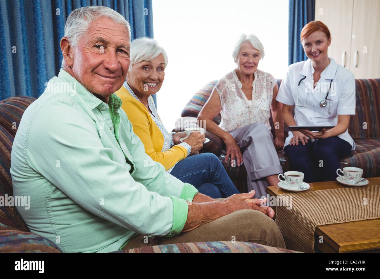 Portrait of smiling retired person looking at the camera - Stock Image