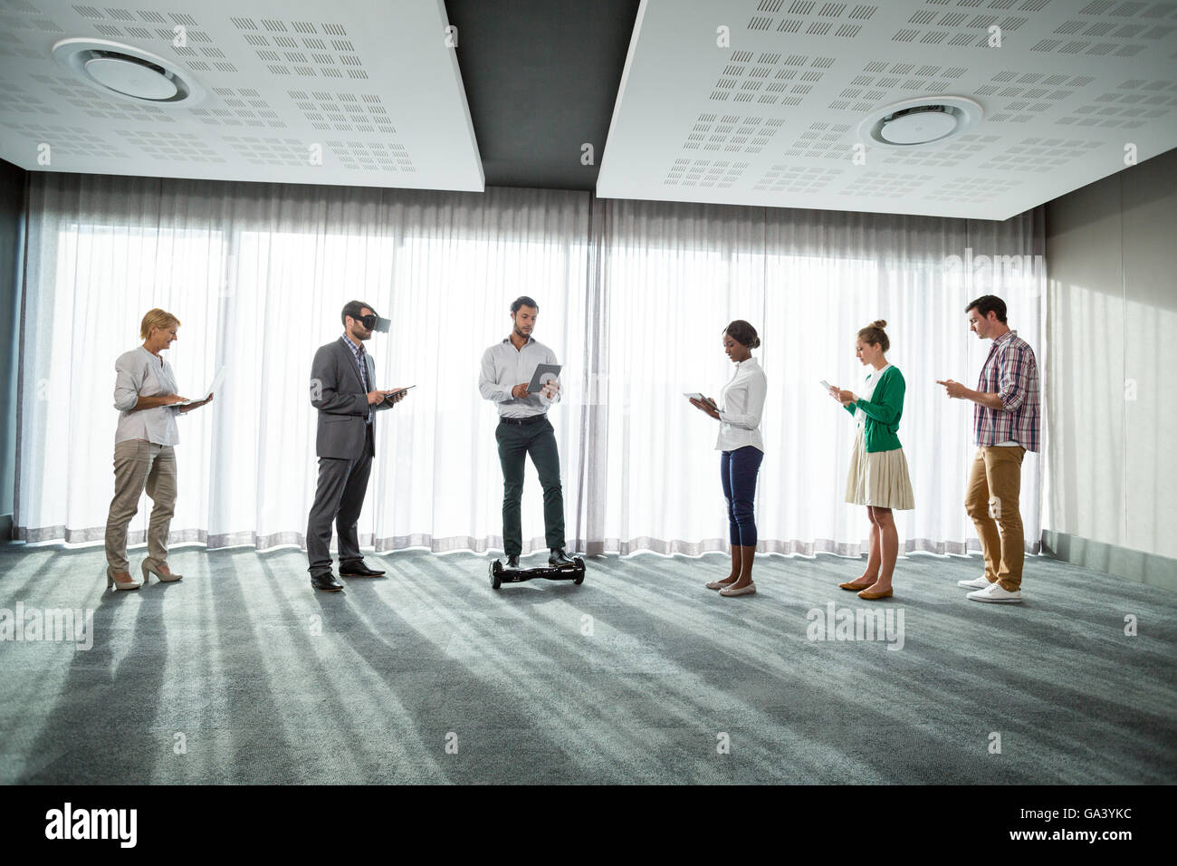 Business people using electronic gadgets - Stock Image