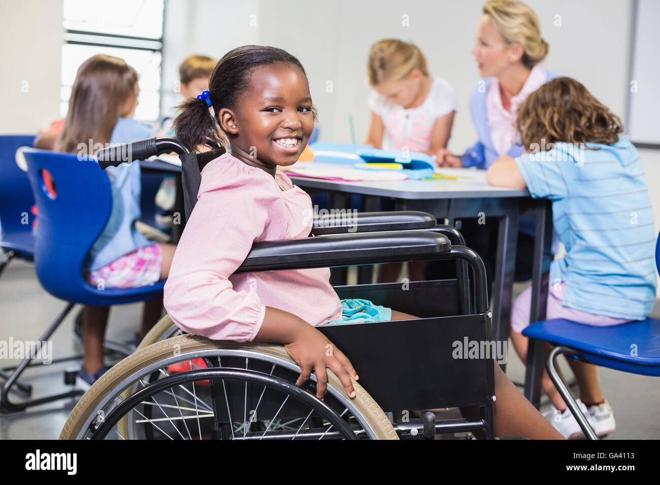 Disabled schoolgirl smiling in classroom - Stock Image