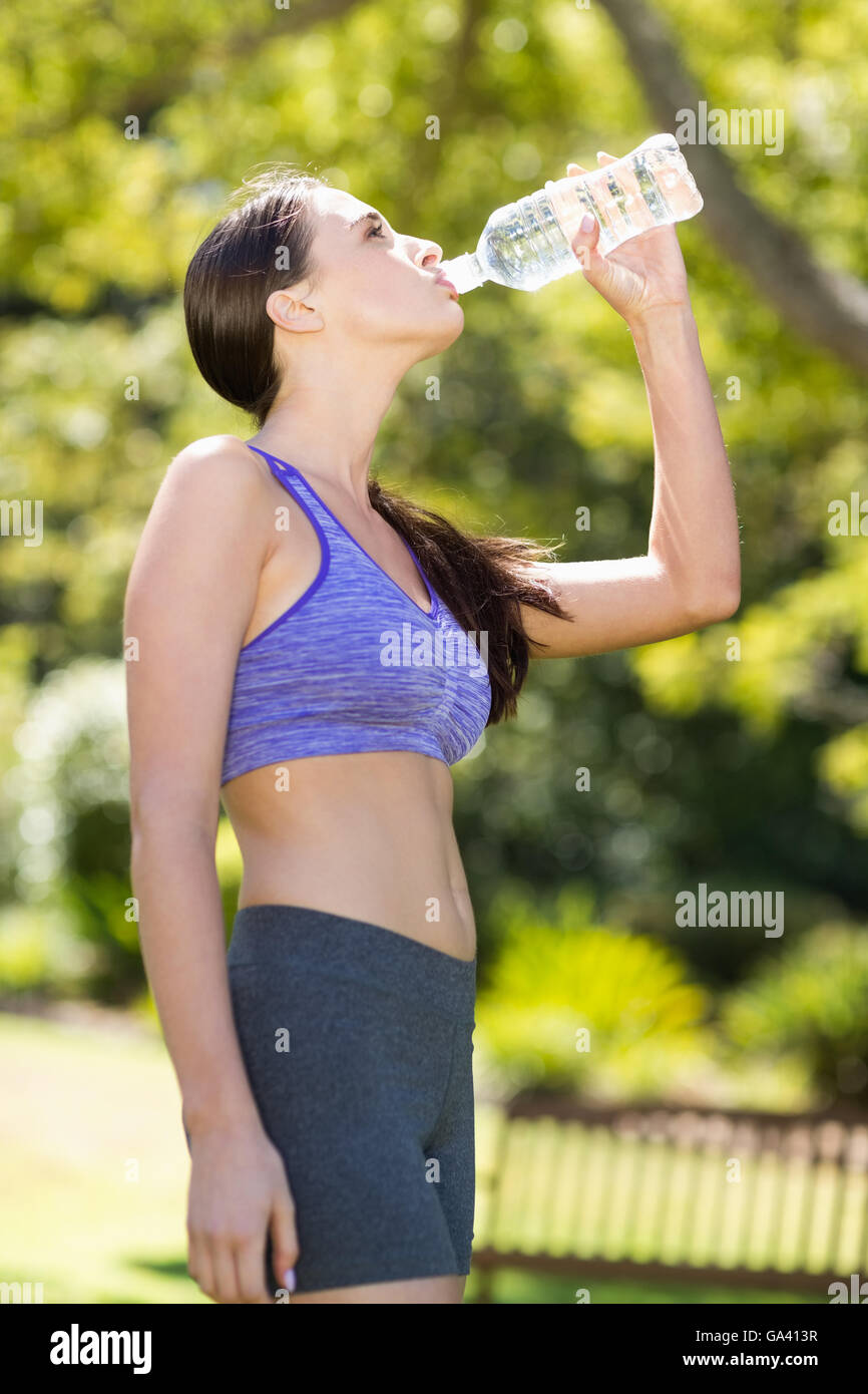 Woman drinking water from water bottle - Stock Image