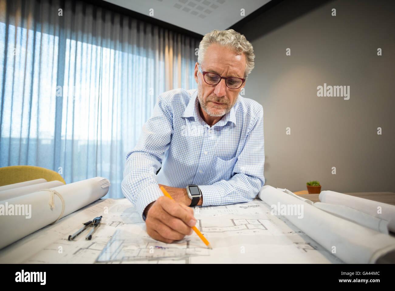 Architect working on blueprint at desk - Stock Image