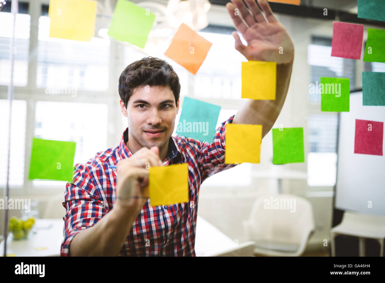 Businessman writing on multi colored sticky notes - Stock Image