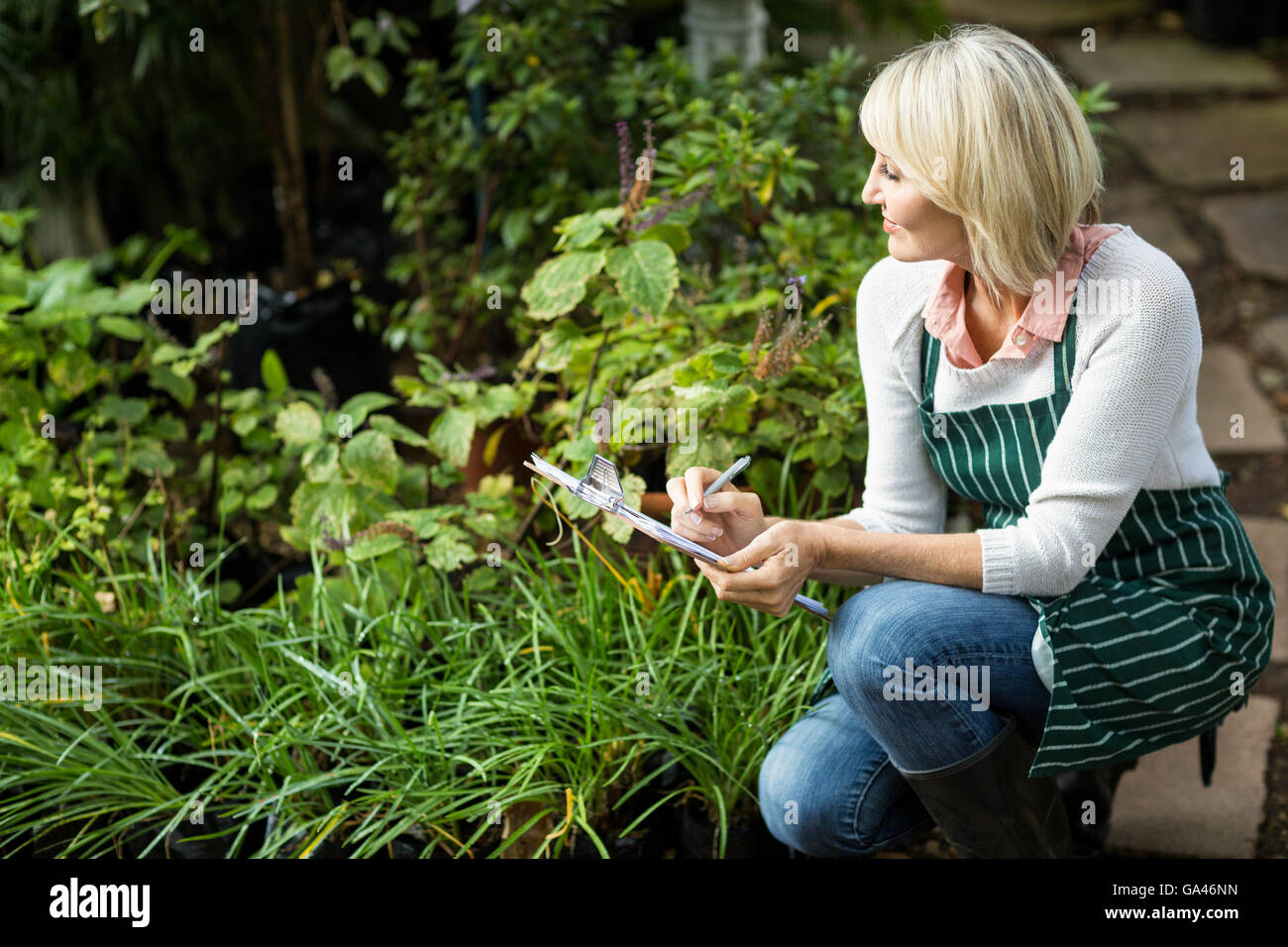 Woman writing on clipboard while examining plants - Stock Image