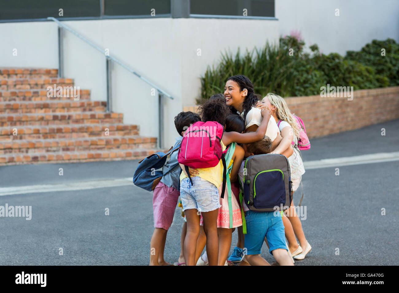 Schoolchildren embracing teacher - Stock Image