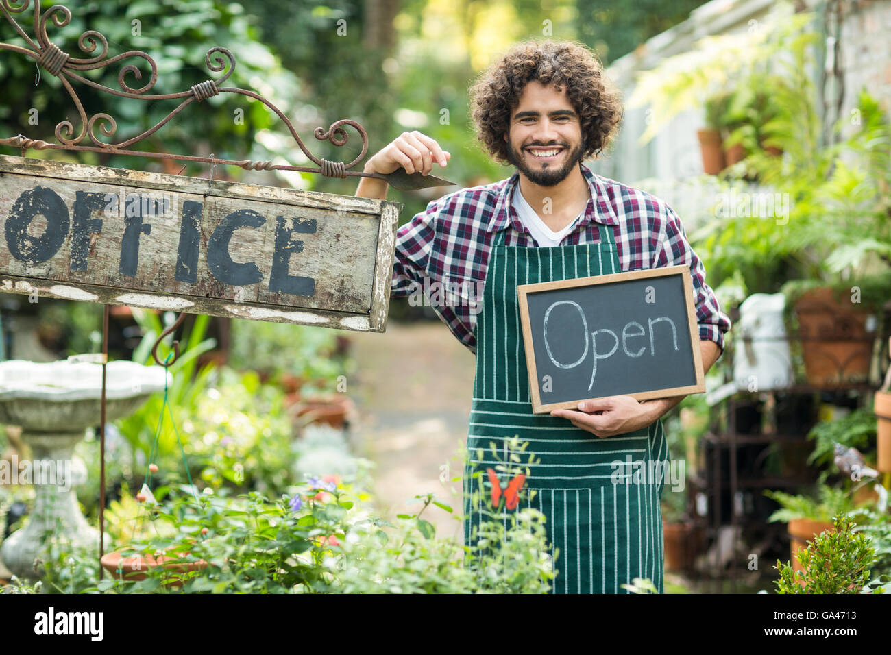 Male gardener holding open sign by office placard - Stock Image