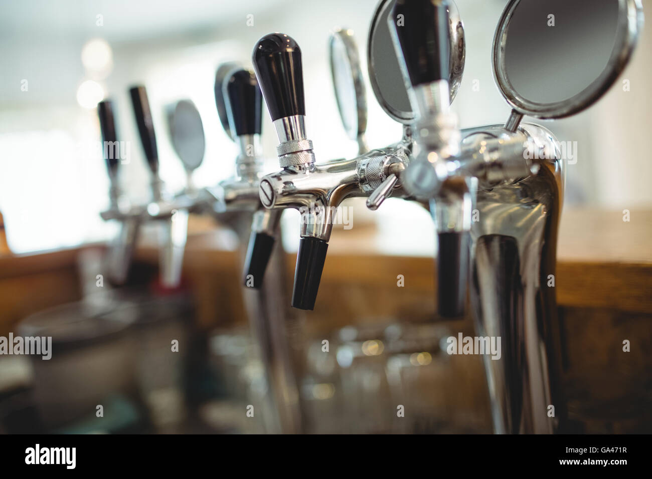 Row of beer taps at cafe - Stock Image