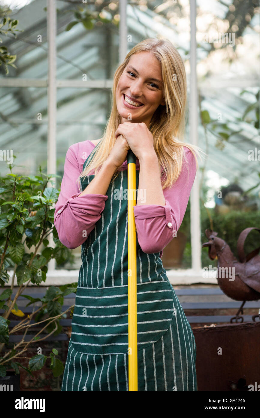 Portrait of beautiful gardener with work tool against greenhouse - Stock Image