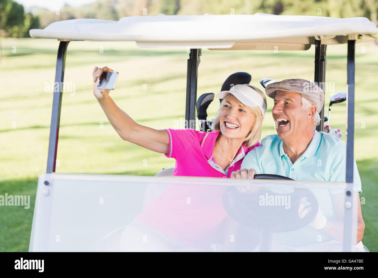 Couple taking selfie while sitting in golf buggy - Stock Image