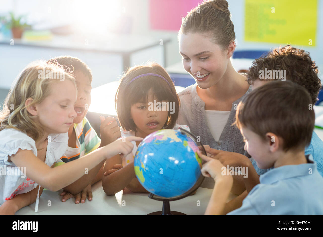 Teacher looking at schoolchildren touching globe - Stock Image