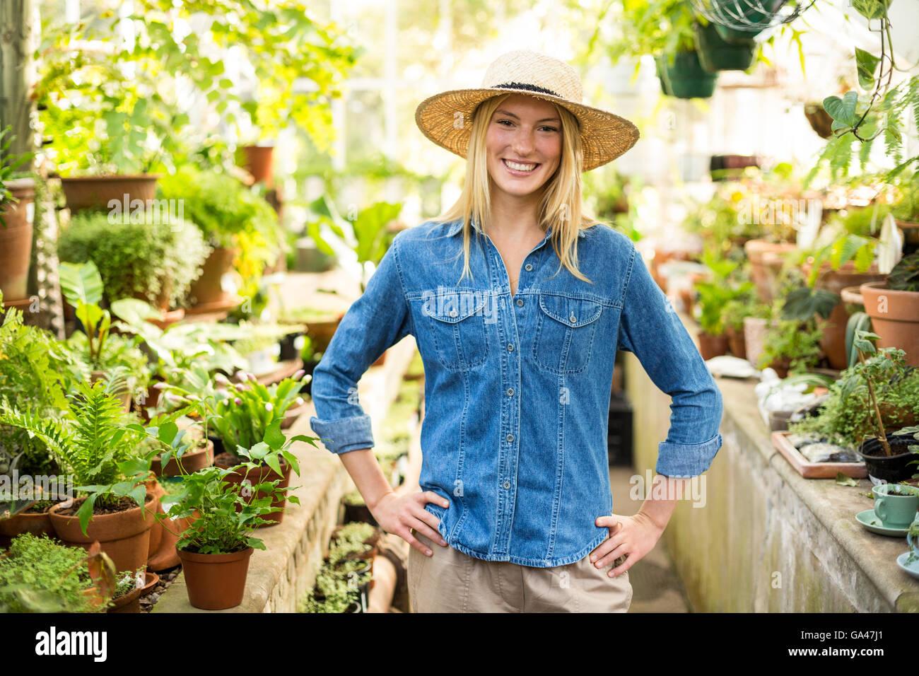confident female gardener at greenhouse - Stock Image