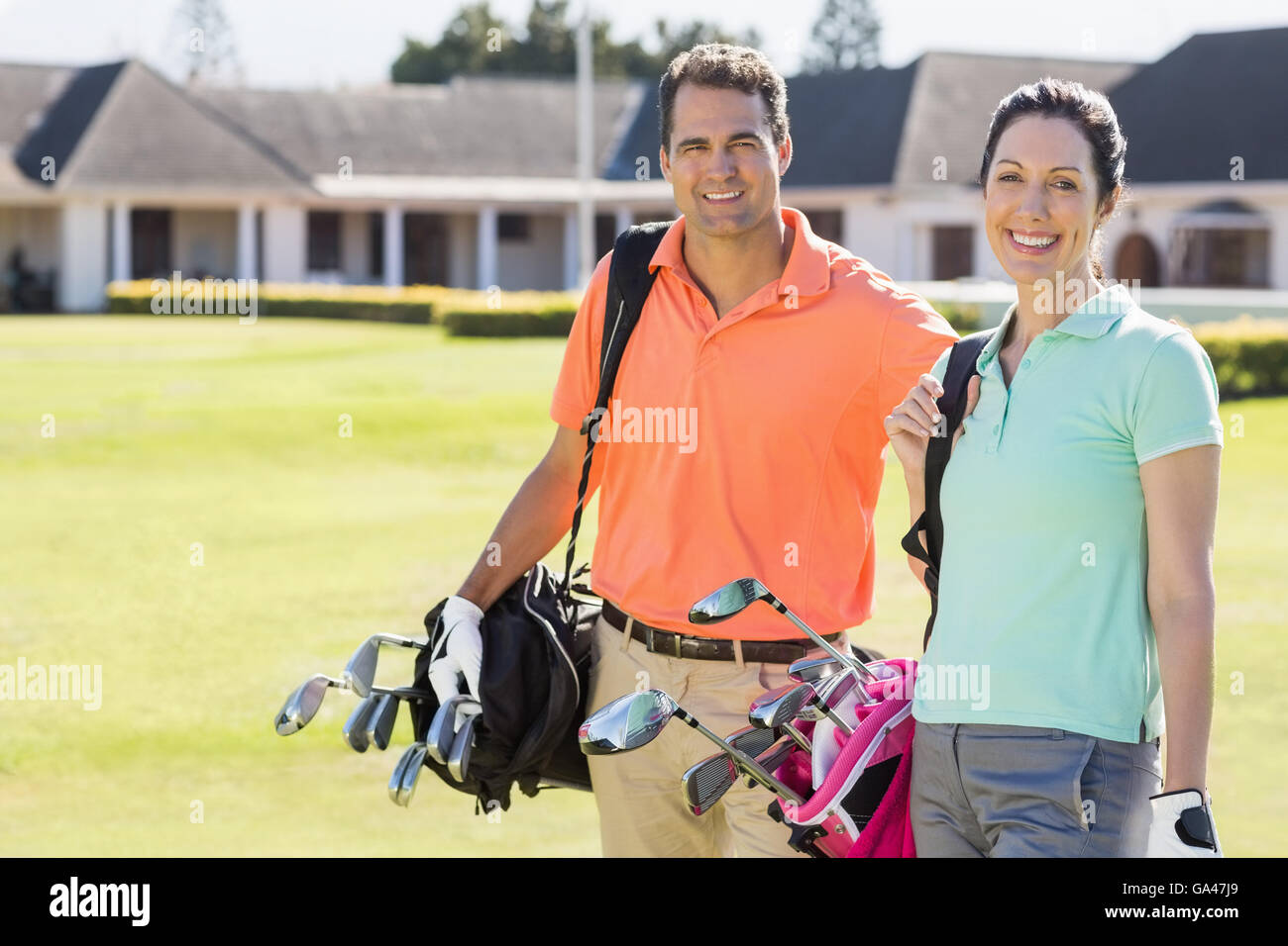 Portrait of couple carrying golf bags - Stock Image