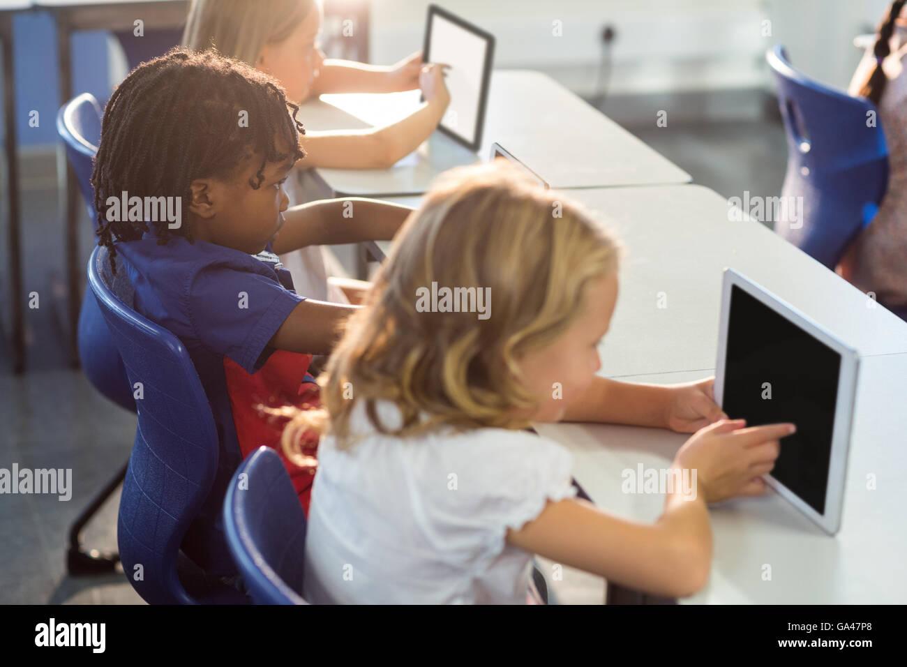 Schoolchildren using digital tablets - Stock Image