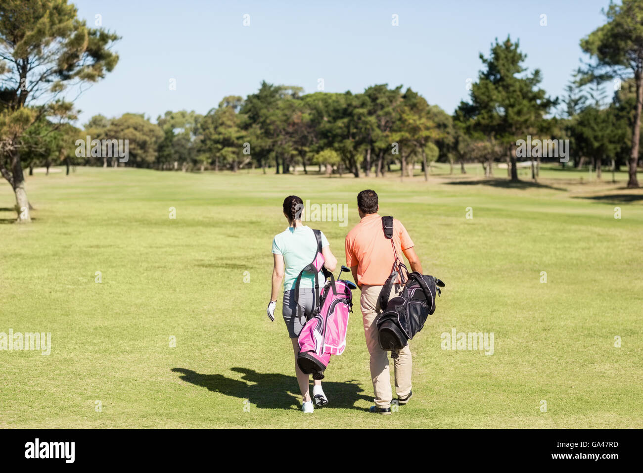 Rear view of couple carrying golf bags - Stock Image