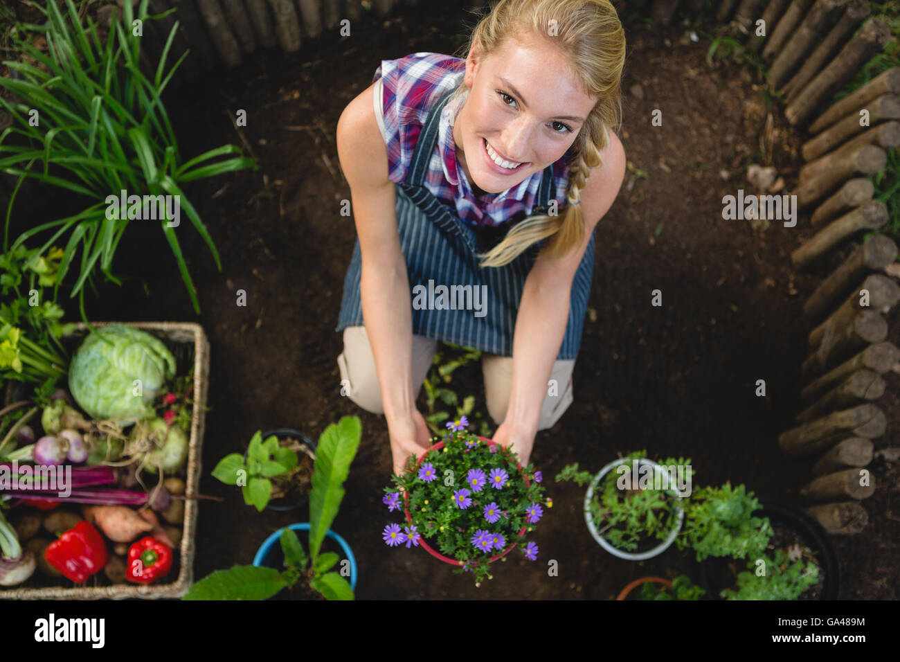 Portrait of happy gardener with potted plant at garden - Stock Image