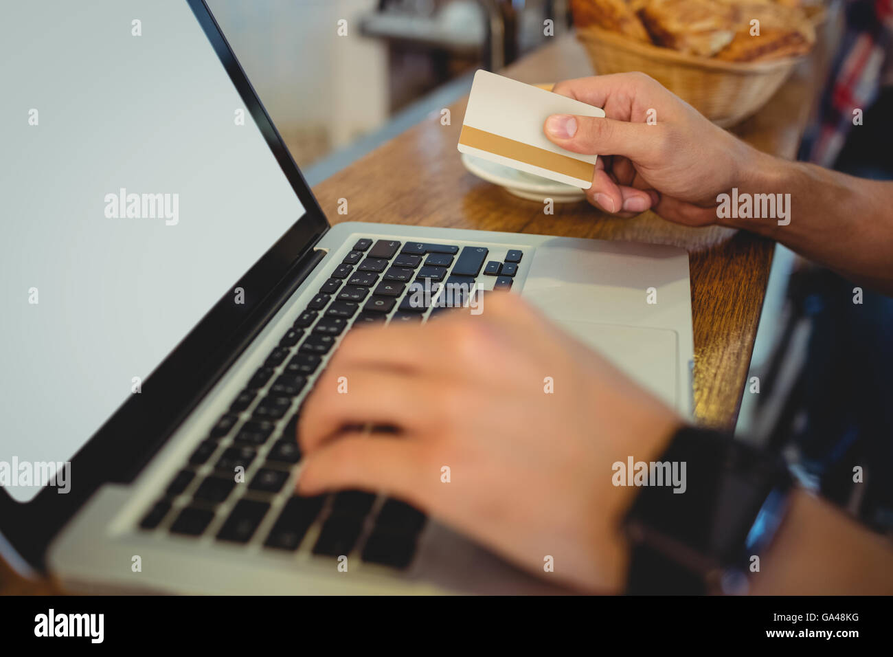 Close-up of customer spending money on online at cafe - Stock Image