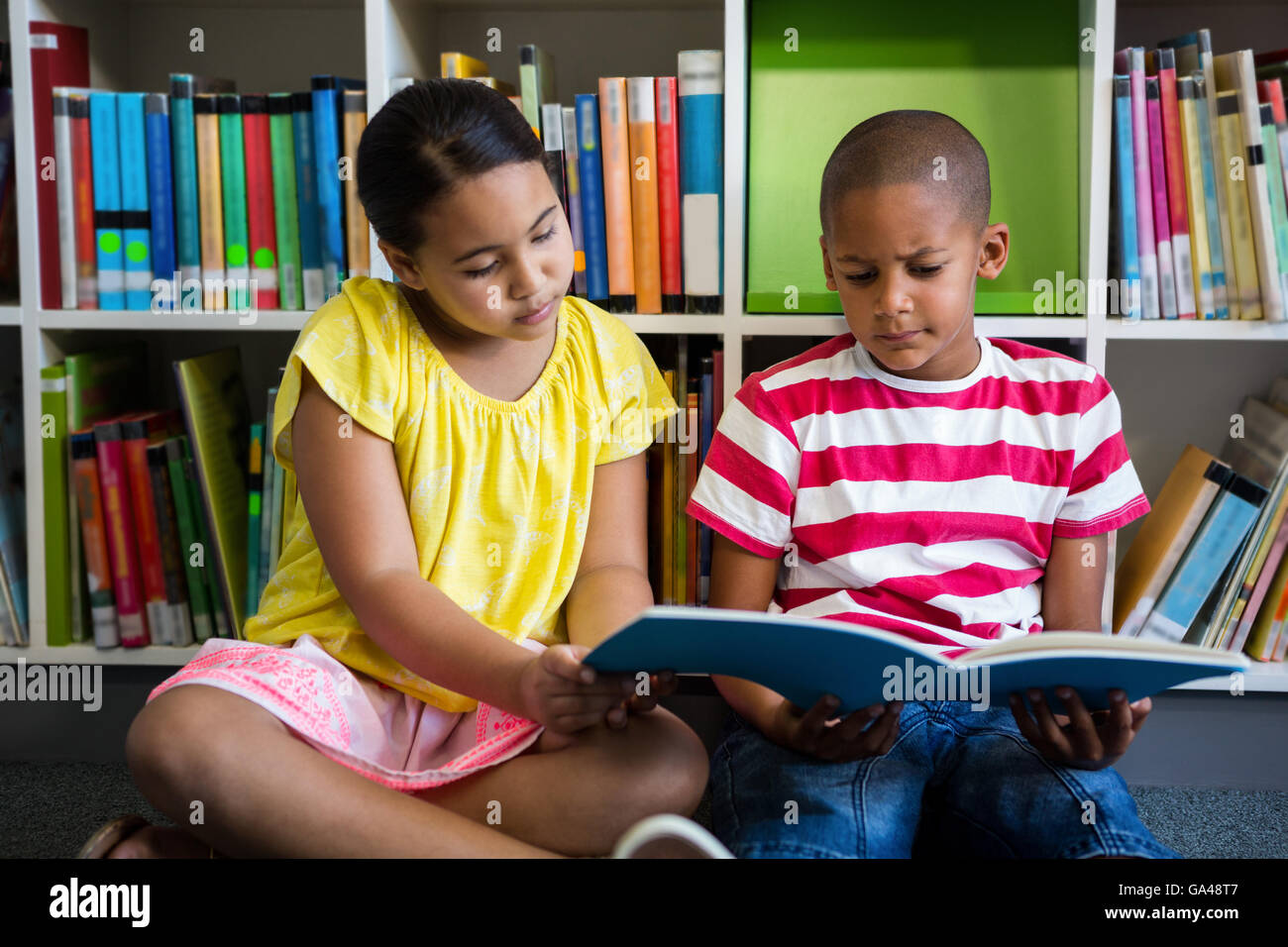 Elementary students reading book at library in school - Stock Image