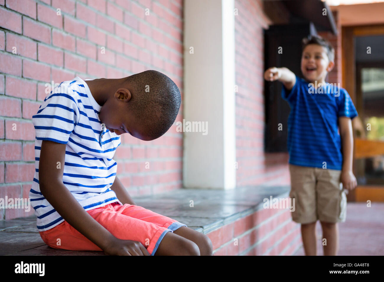 Boy laughing on sad classmate in corridor - Stock Image