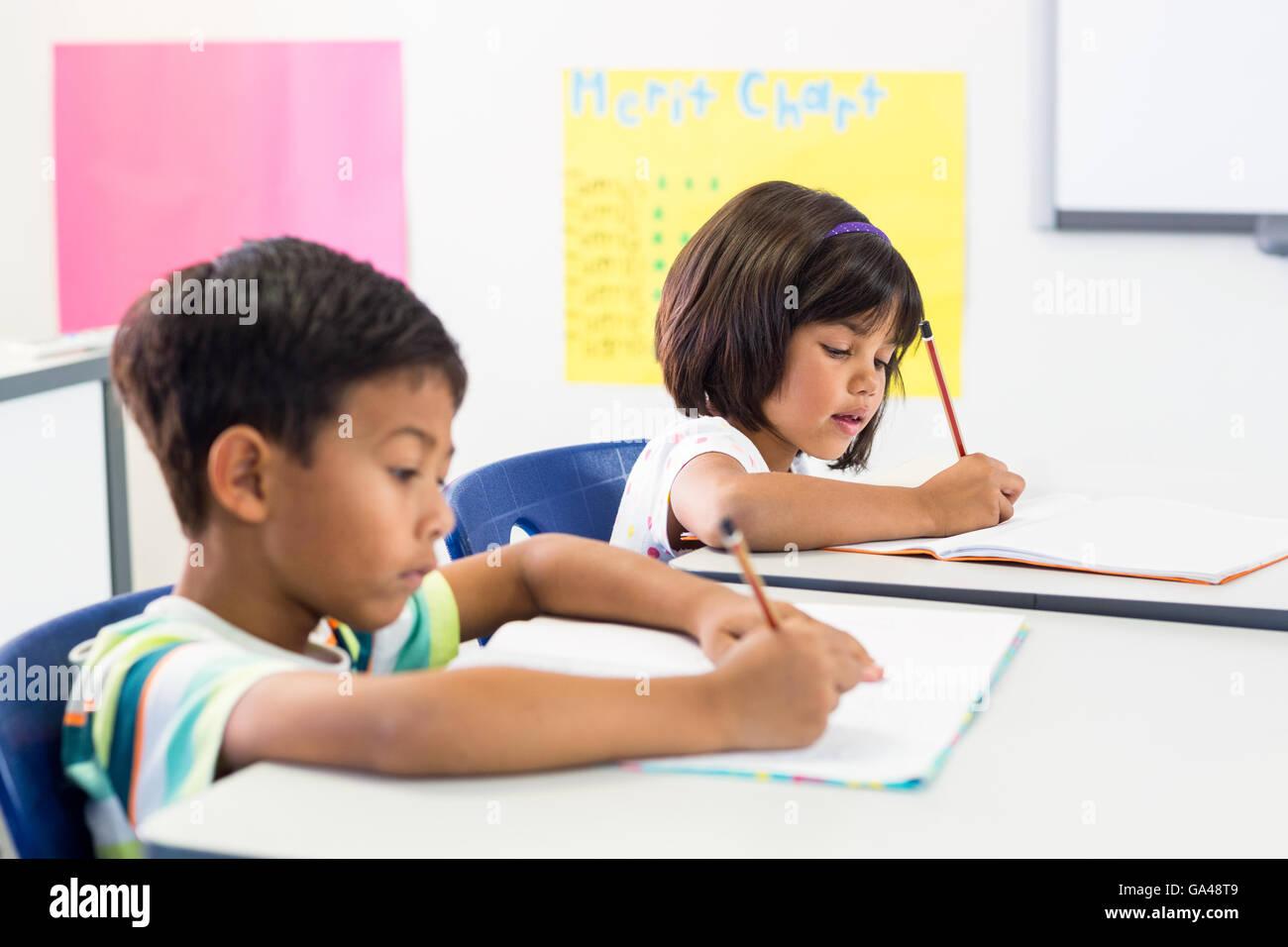 Schoolchildren writing on books - Stock Image