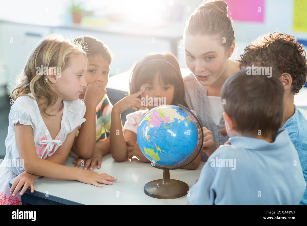 Teacher showing globe to schoolchildren - Stock Image