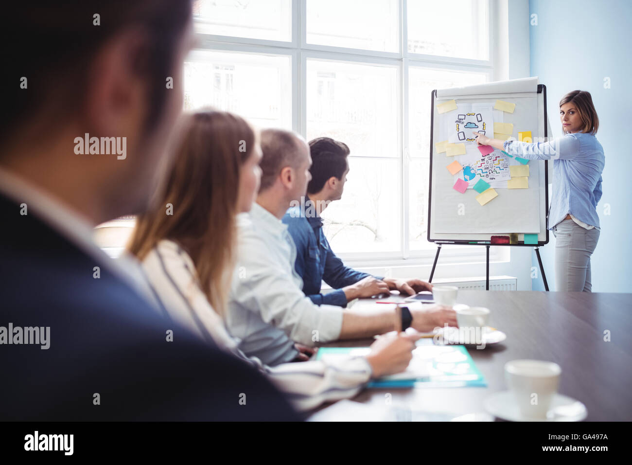 Businesswoman giving presentation in meeting room - Stock Image